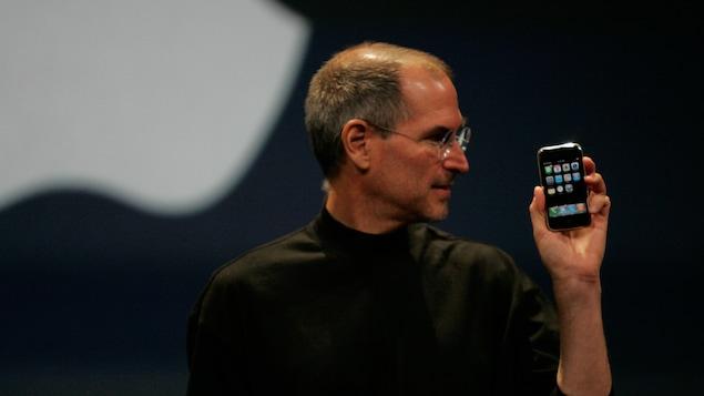 Steve Jobs avec un iPhone en main
