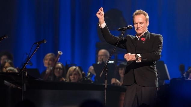 Élégamment vêtu d'un veston noir, Sting chante et danse sur fond de lumière bleutée.