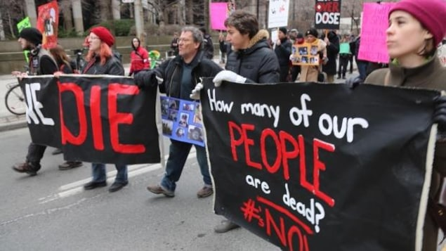 Des gens qui marchent avec des bannières et des photos de proches qui sont morts.