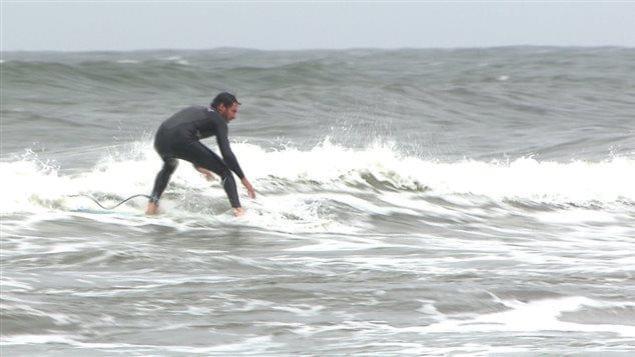Un surfeur profite des vagues à Sept-Îles.