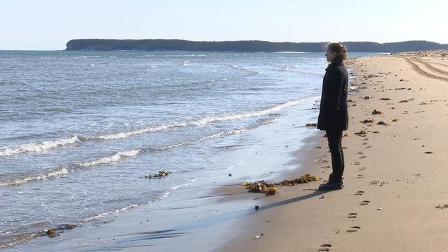 L'auteure jeunesse Tania Boulet est sur la plage, le regard tourné vers la mer.