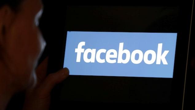 Une femme regardant le logo de Facebook sur une tablette électronique.
