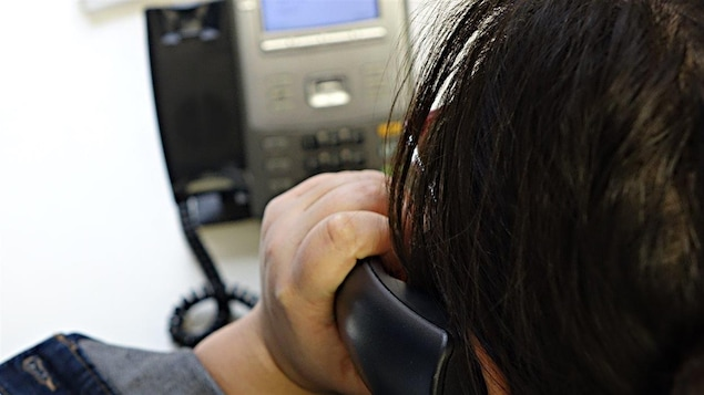 Une femme utilise un téléphone filaire à son bureau