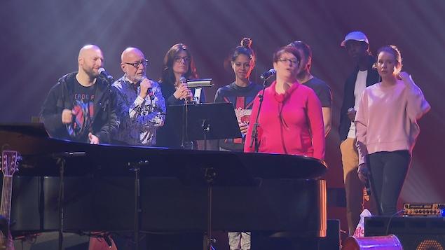 On voit des artistes avec un micro en main. Il sont positionnés derrière un piano à queue sur une scène d'une salle de spectacle.