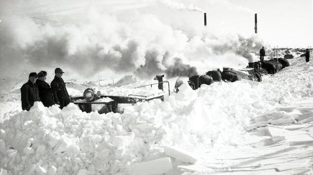 Un train enlisé dans la neige à Rouyn-Noranda lors de la grande tempête de 1947. En arrière plan, la mine Noranda.