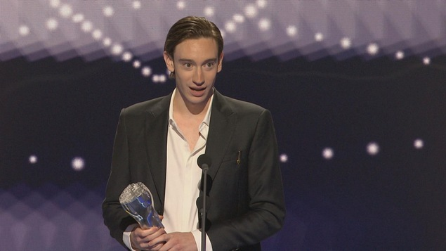 L'acteur est debout sur scène et fait son discours de remerciement.