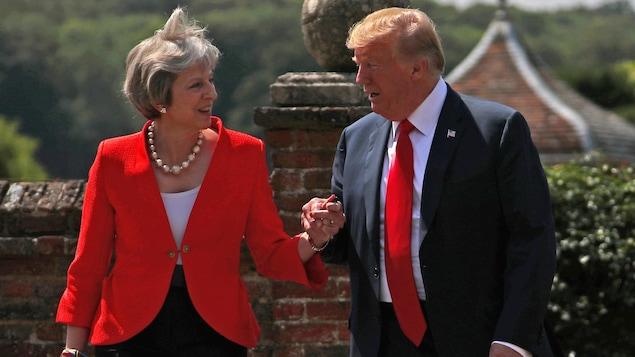Theresa May et Donald Trump s'empoignent la main.