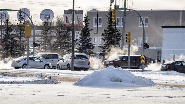 Des voitures circulent au centre-ville de Thompson au Manitoba en hiver.
