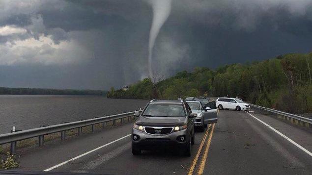 Une file de voitures et derrière une tornade.
