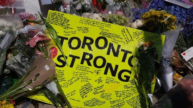 Une carte jaune « Toronto Strong »  et couverte de nombreux messages, déposée au milieu des fleurs sur les lieux de l'attaque mortelle à Toronto.