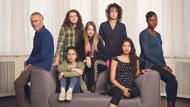 Les sept personnes sont assises ou se tiennent debout près d'un divan.