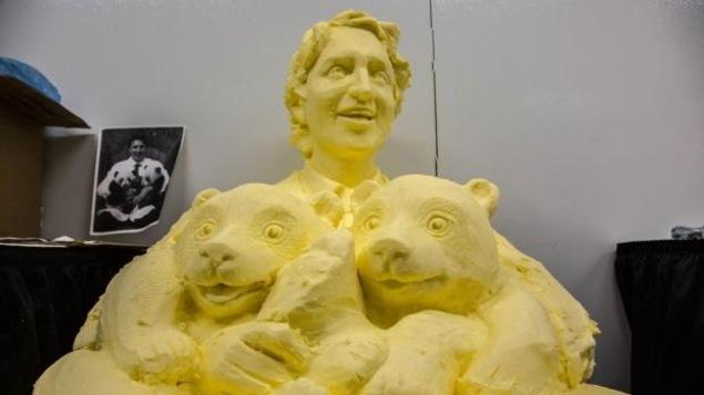 Photo de la sculpture en beurre de Justin Trudeau tenant les deux bébés pandas dans ses bras.