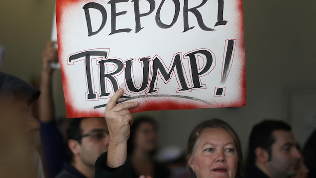 Une femme tient une pancarte anti-Trump lors d'une manifestation à Miami contre l'interdiction visant les musulmans.