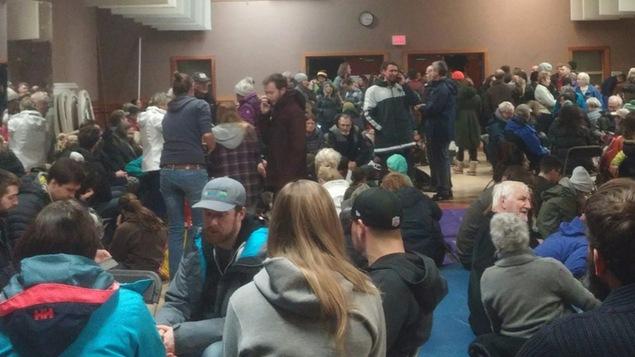 Des gens rassemblés dans une salle.