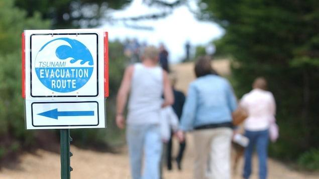 On voit au premier plan un panneau où il est écrit « route d'évacuation en cas de tsunami ». En arrière-plan, des gens marchent pour se rendre à un point de rendez-vous.