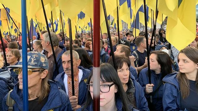 Des gens sont rassemblés et tiennent des drapeaux ukrainiens.