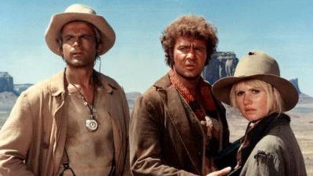 Les trois personnes sont dans le désert et paraissent surprises.
