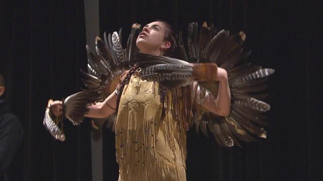 Une femme habillée d'un habit traditionnel autochtone porte des plumes. Elle danse sur une scène.