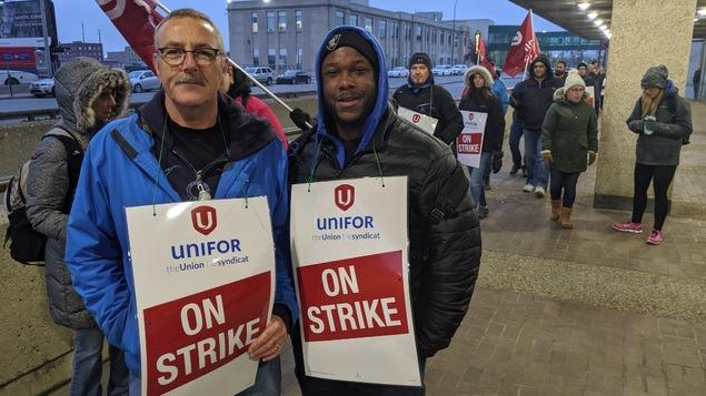 Deux hommes posent avec une pancarte où on peut lire « On strike ».