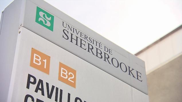 Une pancarte de l'Université de Sherbrooke située devant un pavillon