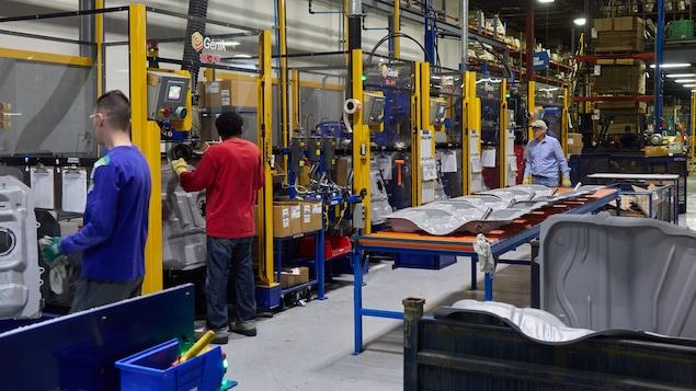 Des ouvriers qui utilisent des machines, dans l'usine Spectra Premium de Boucherville.