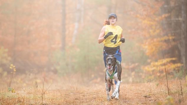 Une femme qui court avec son chien sur un sentier.