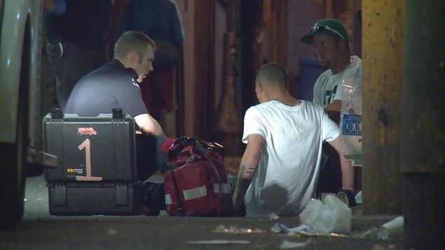 vancouver un policier avec sa trousse de naloxone pour aider un homme à terre