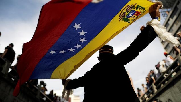 Un homme tient derrière lui un drapeau du Venezuela lors d'une manifestation le 24 juillet 2017