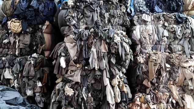 Des piles de vêtements de couleur gris sont dans un entrepôt.