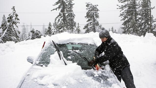 Une femme déneige sa voiture.