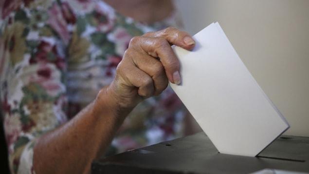 Une femme dépose son bulletin de vote dans une urne.