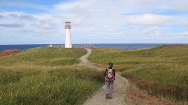 Joëlle Pineault marche vers un phare aux Îles-de-la-Madeleine.