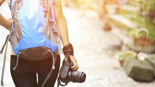 Une femme portant un sac à dos et un appareil photo