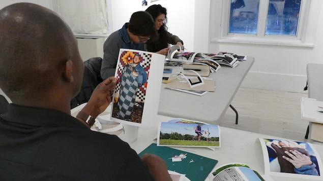 Wilgis Agossa regarde une photo d'une homme blanc vêtu en habit africain.