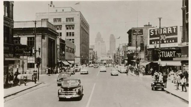 Une rue achanlandée, des automobiles circulent. Au loin, on aperçoit les gratte-ciel de Détroit.