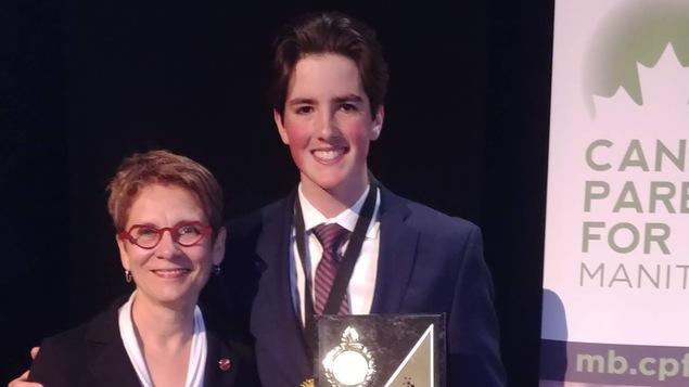 Un jeune homme, tenant un trophée, prend la pose aux côtés d'une femme.