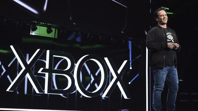 Phil Spencer sur une scène devant le logo de Xbox.