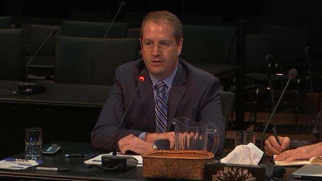 Un homme aux cheveux courts et châtains porte des lunettes rectangulaires beiges et est vêtu d'un complet noir et mauve. Il est assis, les bras  appuyés sur la table devant lui et il parle dans un micro.
