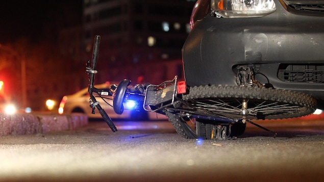 Une bicyclette est coincée sous la roue d'une automobile.