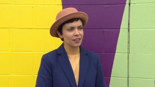 L'artiste visuelle Zoé Fortier qui porte un chapeau devant dehors devant une peinture murale colorée.