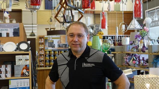 Alain Leblanc pose dans son magasin et arbore un chandail de son entreprise