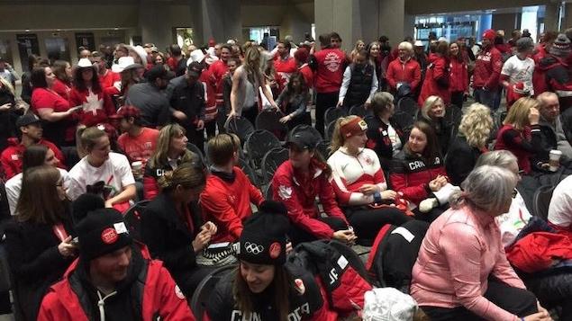 Des athlètes canadiens vêtus de vêtements aux couleurs du Canada sont réunis devant le salle du conseil municipal de la ville de Calgary.