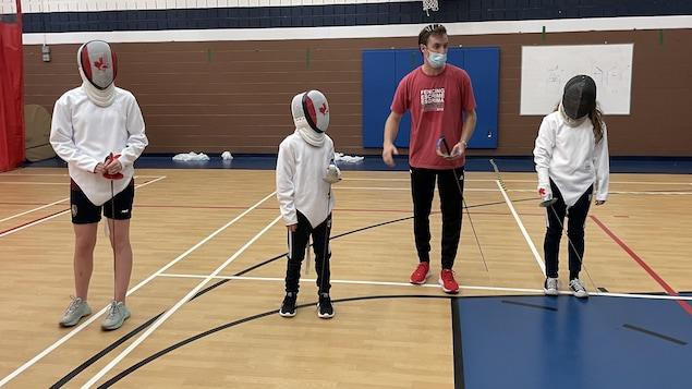 Un entraîneur d'escrime donne des directives à de jeunes athlètes dans un gymnase. Il porte un chandail rouge et les escrimeurs sont en blanc avec un masque de protection.