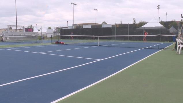 un court de tennis à Gatineau où on peut voir un joueuse s'élancer pour un service