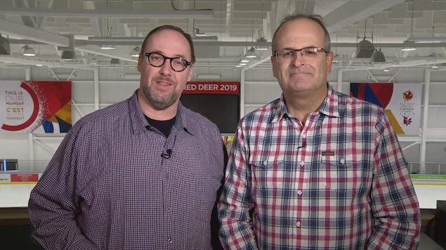 Deux hommes côte à côte dans un aréna.