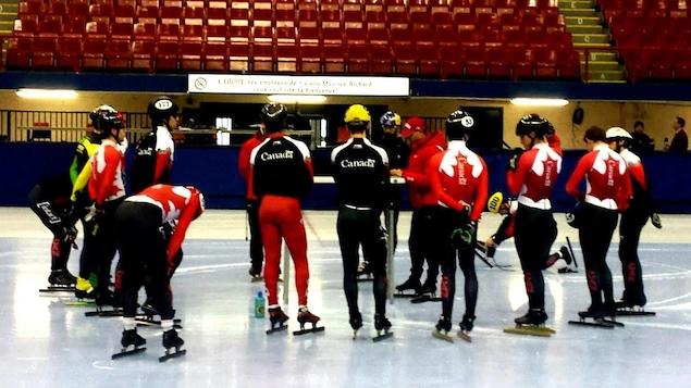 L'équipe canadienne masculine de courte piste écoute les instructions de l'entraîneur-chef Derrick Campbell à l'aréna Maurice-Richard.