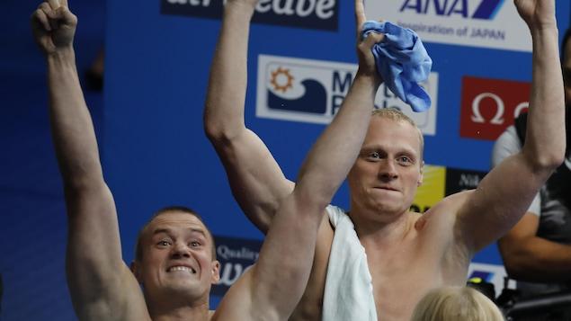 Les plongeurs russes Ilya Zakharov (à gauche) et Evgenii Kuznetsov célèbrent leur victoire au 3 m masculin synchronisé au 17es Championnats mondiaux de la FINA.