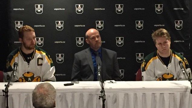 Le capitaine des Golden Bears de l'Université de l'Alberta, Brennan Yadlowski, l'entraîneur-chef Serge Lajoie et l'attaquant Jamie Crooks s'adressent aux médias à la suite de la défaite subie aux mains des Axemen d'Acadia.