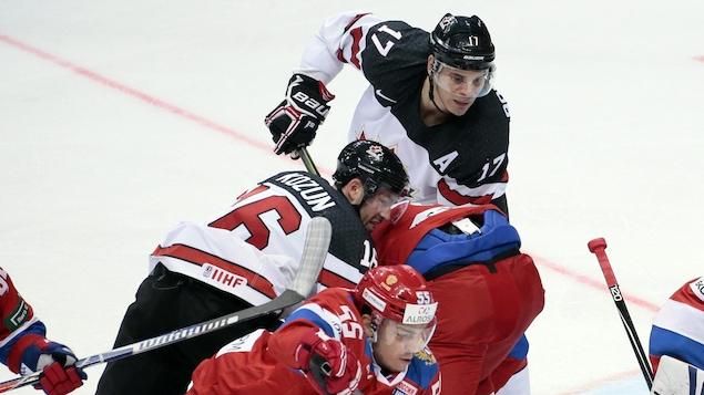 Rene Bourque (au haut de l'image) et Brandon Kozun (à gauche) tentent de se défaire de leurs adversaires russes à la Coupe Channel One, à Moscou.