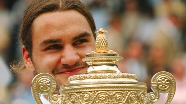 Roger Federer, souriant, avec le premier trophée qu'il a gagné à Wimbledon, en 2003